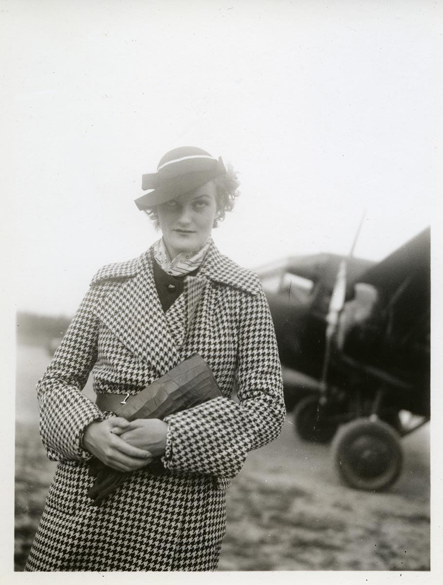 Doris Duke standing in front of small clipper plane