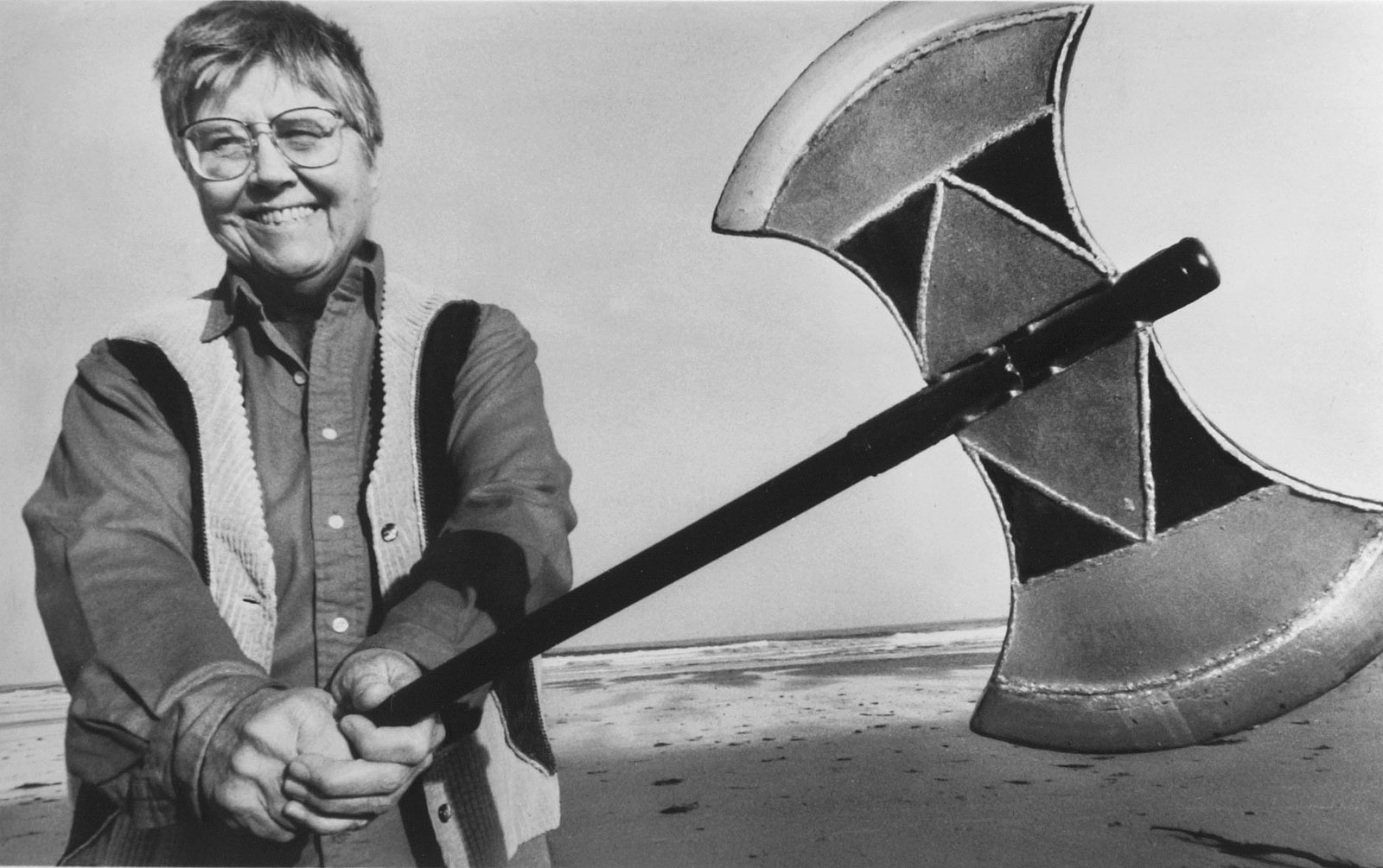 Photo of feminist Mary Daly holding an axe